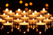 selective focus of burning candles glowing in darkness with bokeh lights