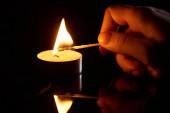 Fotografie selektivní zaměření ženy zapalování svíčky se zápalkou izolované na černé