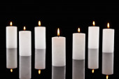 selective focus of burning white candles glowing isolated on black