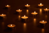 selective focus of burning white candles glowing in dark