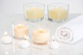 pálení bílých svíček ve skle a válcované ručník na mramorovém bílém povrchu