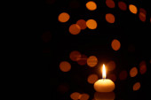 Photo burning candle glowing in dark with bokeh lights on background