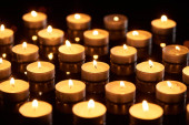 selective focus of burning candles glowing in darkness