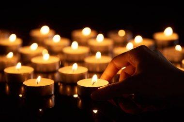 selective focus of woman holding burning candle in darkness