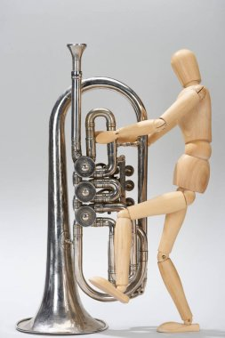 Wooden puppet with alto horn on grey background