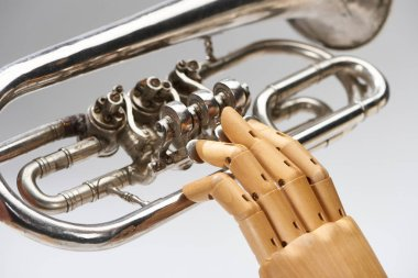 Close up view of wooden hand of doll with alto horn isolated on grey