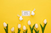 top view of tulips, greeting card with happy Easter lettering near Easter white bunnies on yellow colorful background