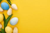 horní pohled na tulipány a malované velikonoční vajíčka na barevném žlutém pozadí s kopírovacím prostorem