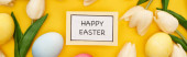 Fényképek top view of tulips and painted Easter eggs around card with happy Easter lettering on colorful yellow background, panoramic shot