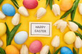 top view of tulips and painted Easter eggs around card with happy Easter lettering on colorful yellow background