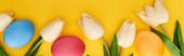 horní pohled na tulipány a malované velikonoční vajíčka na barevném žlutém pozadí, panoramatický záběr