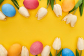 top view of tulips and painted Easter eggs on colorful yellow background with copy space