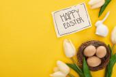 Fotografie horní pohled na tulipány, pohlednice se šťastným velikonočním písmem, velikonoční zajíček a vejce v hnízdě na žlutém barevném pozadí