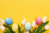 horní pohled na tulipány a malované velikonoční vajíčka na barevném žlutém pozadí