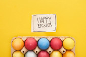 Ansicht von bemalten Eiern in Schachtel und Grußkarte mit fröhlichem Osteraufdruck auf gelbem, buntem Hintergrund