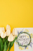 Fotografie top view of spring tulips and happy mothers day greeting card on colorful yellow background