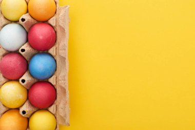top view of multicolored painted Easter eggs in cardboard container on yellow background with copy space