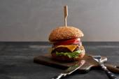 vynikající čerstvé maso cheeseburgery na dřevěné desce v blízkosti příbory