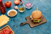 frisch gekochter Burger auf hölzernem Schneidebrett in der Nähe von Zutaten auf blauer strukturierter Oberfläche
