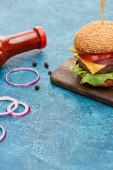 köstliche Cheeseburger auf Holzbrett in der Nähe von Zwiebeln und Ketchup auf blau strukturierter Oberfläche