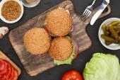 Blick von oben auf leckere frische Burger in der Nähe von Zutaten und Besteck auf dem Holzschneidebrett