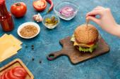 oříznutý pohled ženy vaření lahodný čerstvý burger na modrém texturovaném povrchu