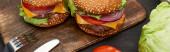 leckere frische Cheeseburger auf Holzbrett mit Besteck, Panoramaaufnahme