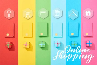 Top view of multicolored empty credit cards and gift boxes on rainbow background with online shopping illustration stock vector