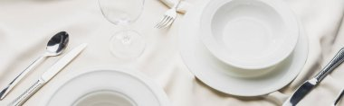 Panoramic shot of serving tableware with wine glass on white tablecloth