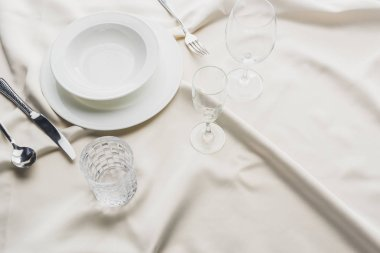 High angle view of serving tableware with glasses on white tablecloth