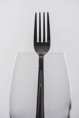 Selective focus of fork in wine glass isolated on grey stock vector