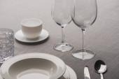 Tiszta borospoharak edények és kávéscsésze mellett szürke ruhán