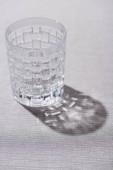 Čiré texturované sklo se stínem na šedé látce