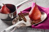 vynikající hruška ve víně se skořicí a anýzem na stříbrném talíři a v hrnci na šedém betonovém povrchu s růžovým ubrouskem, nožem a vidličkou