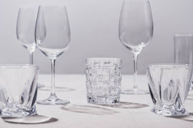 Empty glasses on white tablecloth isolated on grey stock vector