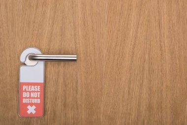 Wooden hotel room door with please do no disturb sign on handle stock vector
