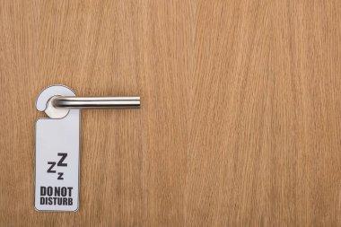 Wooden hotel room door with do no disturb sign on handle stock vector