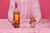 Photo cropped view of woman holding bottle of alcohol drink and glass at velour pink table isolated on pink, girlish concept