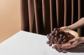 levágott kilátás nő gazdaság fonott kosár szőlő az asztalon közelében függöny elszigetelt bézs, csendélet koncepció