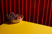 classic still life with fruits in wicker basket on yellow table near red curtain