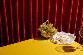 classic still life with Camembert near glass of red wine and grape on yellow table near red curtain