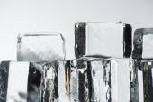 Nahaufnahme von schmelzenden transparenten, quadratischen Eiswürfeln isoliert auf weißen