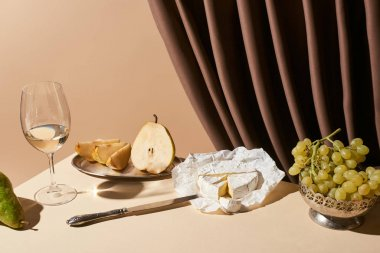 Classic still life with pears, grape, white wine and Camembert cheese on table near curtain isolated on beige stock vector