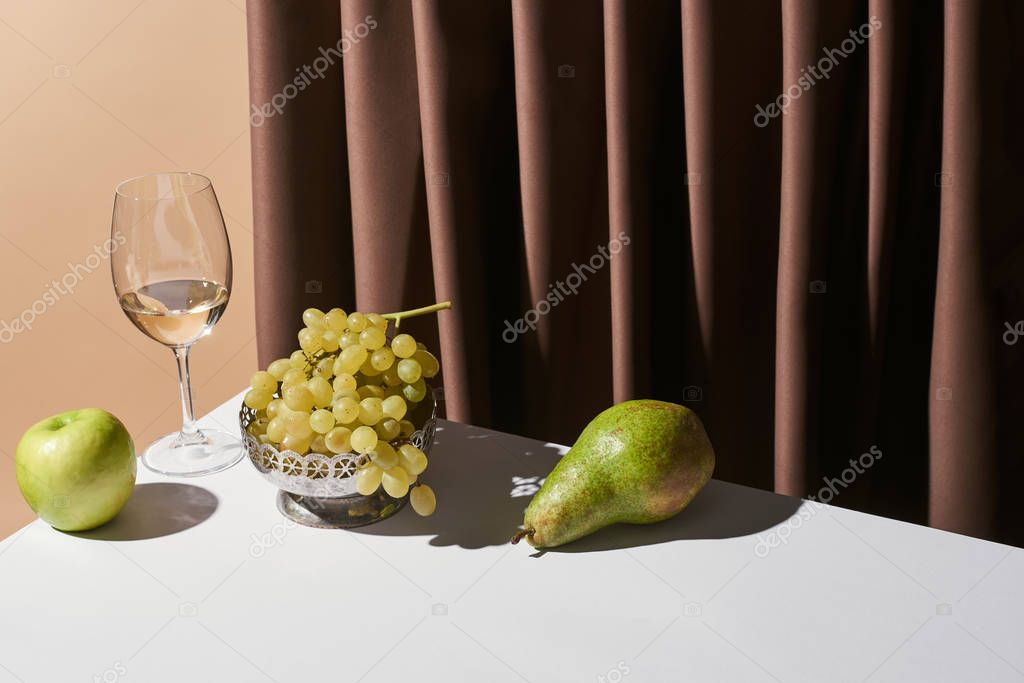 Classic still life with white wine and fruits on table near curtain isolated on beige stock vector