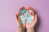 oříznutý pohled na ženu držící barevné papírové srdce na fialovém pozadí