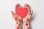 Fotografie Ausgeschnittene Ansicht einer Frau mit roten Herzen auf weißem Hintergrund