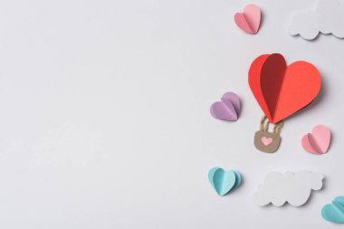 Top view of colorful paper hearts and air balloon with clouds on white background stock vector