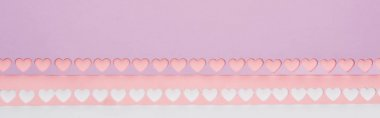 Top view of pink, violet paper with cut out hearts on white background, panoramic shot stock vector