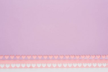 Top view of pink, violet paper with cut out hearts on white background stock vector