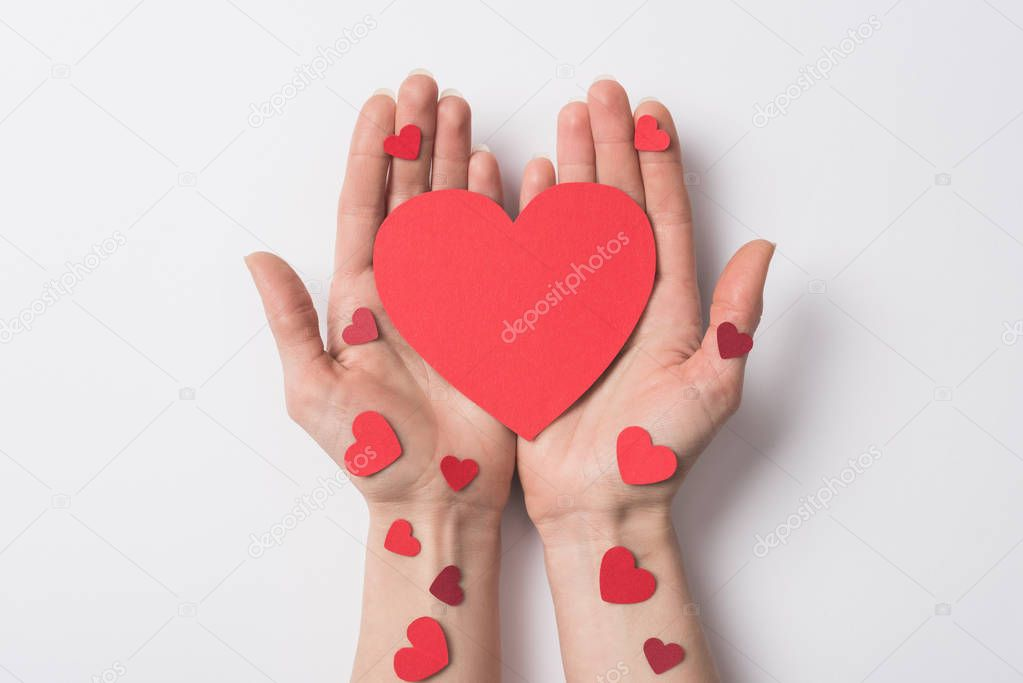 Cropped view of woman holding red hearts on white background stock vector